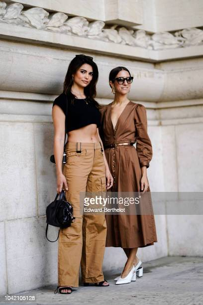 A guest wears a black bare belly cropped top brown pants a black bag a guest wears a brown dress outside Paco Rabanne during Paris Fashion Week...