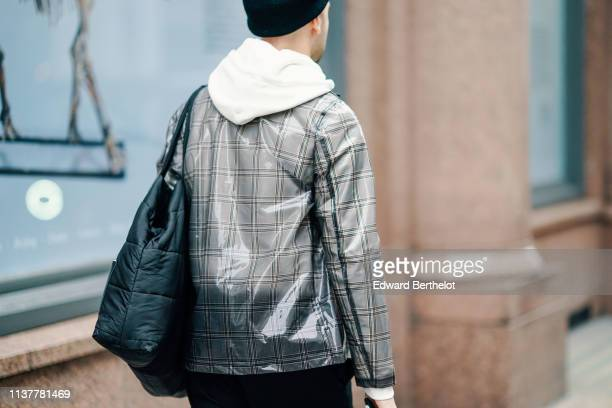 A guest wears a black beanie hat a black padded bag a grey vinyl checkered jacket during London Fashion Week February 2019 on February 16 2019 in...