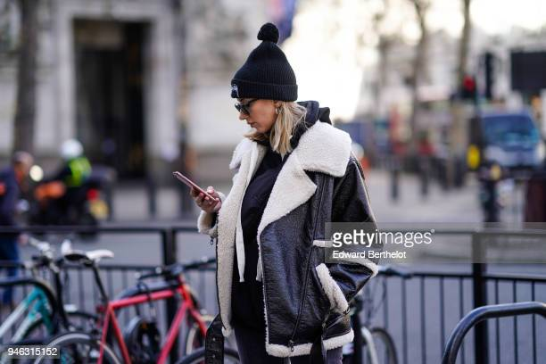 A guest wears a black beanie hat with a pompom an aviator jacket during London Fashion Week February 2018 on February 16 2018 in London England