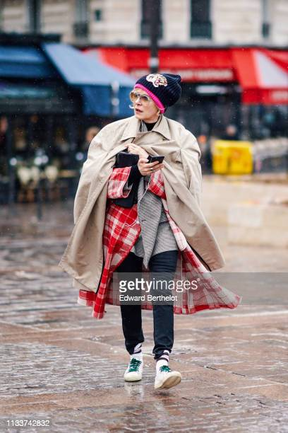 A guest wears a black beanie hat with a tiger head pattern a beige trench coat a red and white checkered coat black pants Vetements socks white...