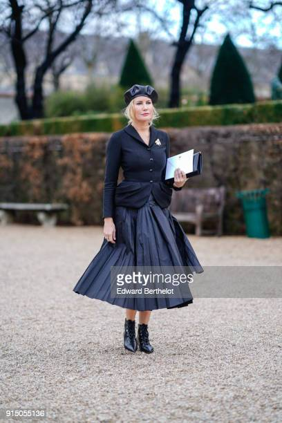 A guest wears a black beret hat a black jacket a black pleated skirt after Dior during Haute Couture Spring/Summer 2018 on January 22 2018 in Paris...
