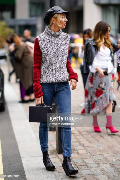 A guest wears a black beret hat a gray wool turtleneck pull over with red sleeves blue jeans outside Preen by Thornton Bregazzi during London Fashion...