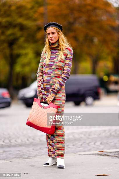 A guest wears a black beret hat a pink and red Chanel bag a multicolor print pattern dress outside Chanel during Paris Fashion Week Womenswear...