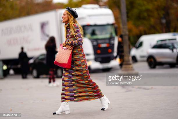 A guest wears a black beret hat a pink Chanel bag a multicolor printed pattern dress white shoes outside Chanel during Paris Fashion Week Womenswear...