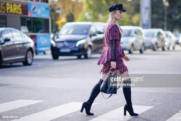 A guest wears a black beret hat a purple tweed dress with fringes black thigh high boots a bag outside Chanel during Paris Fashion Week Womenswear...