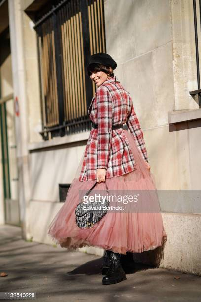 A guest wears a black beret hat a red checkered shirt a black belt a pink vaporous tulle gathered skirt a Dior monogram saddle bag black army boots...