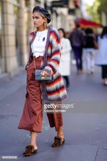 A guest wears a black beret hat a striped cardigan oversize cropped pants brown leopard print shoes with fur a bag outside Acne Studios during Paris...