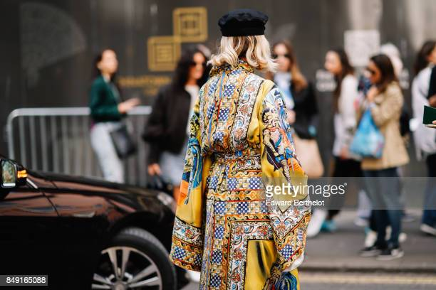 A guest wears a black beret hat a yellow silk outfit with prints outside Topshop during London Fashion Week September 2017 on September 17 2017 in...