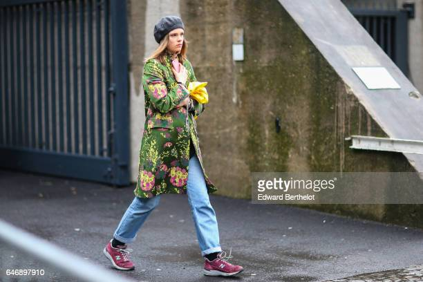 A guest wears a black beret hat and a green jacket with floral print outside the Dries Van Noten show during Paris Fashion Week Womenswear...
