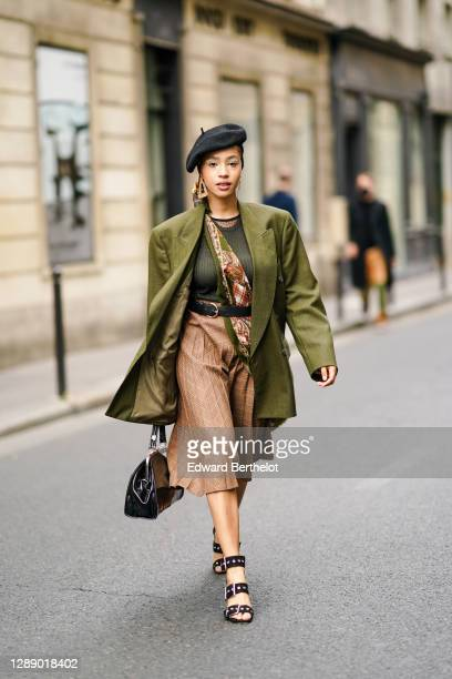 Guest wears a black beret hat, earrings, a green khaki oversized blazer jacket, a mesh top, a floral print scarf, a brown pleated checked skirt, a...