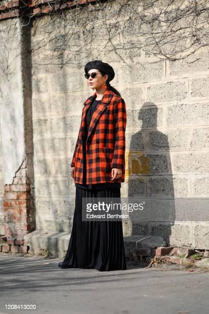 A guest wears a black beret hat sunglasses an orange and black checked pattern oversized blazer jacket a black pleated dress earrings outside BOSS...