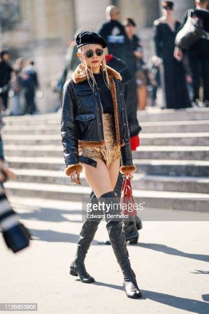 A guest wears a black beret sunglasses a black top golden damask high waist panties a black leather jacket a red bag thigh high separated end black...