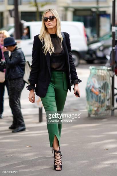 A guest wears a black blazer jacket a black mesh top sunglasses green pants lace shoes outside Miu Miu during Paris Fashion Week Womenswear...