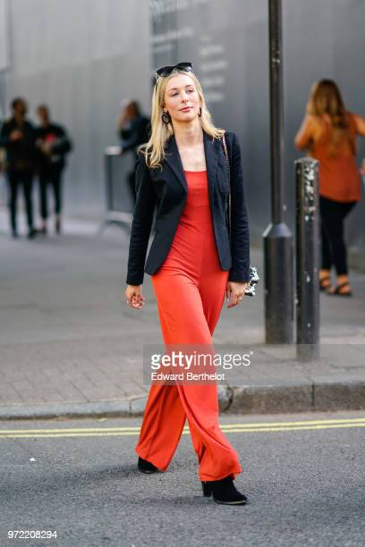 A guest wears a black blazer jacket red flared pants a red top sunglasses during London Fashion Week Men's June 2018 on June 09 2018 in London England