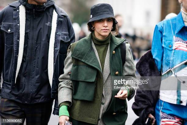 A guest wears a black bob hat an olivegreen turtleneck sweater a grey and green Prince of Wales check jacket a green sleeveless vest with a large...