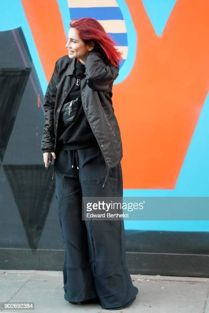 A guest wears a black bomber jacket a black top has red hair during London Fashion Week Men's January 2018 at on January 7 2018 in London England