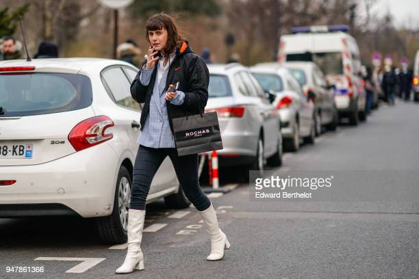 A guest wears a black bomber jacket a shirt black pants white boots during Paris Fashion Week Womenswear Fall/Winter 2018/2019 on February 28 2018 in...