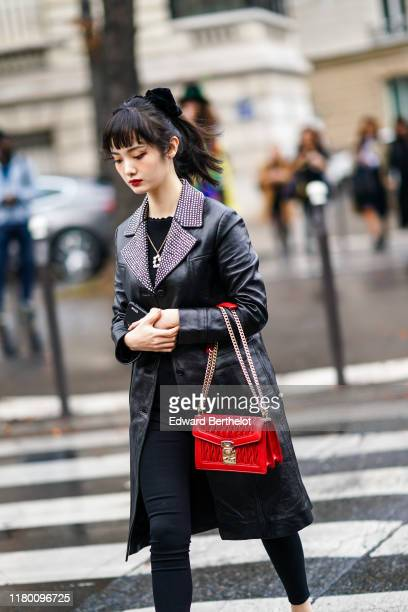 A guest wears a black bow in the hair a black leather coat with a studded collar a scallopedhem collar black top a necklace black leggings a Miu Miu...