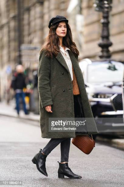Guest wears a black cap, a white broderie anglaise top, a khaki fluffy faux-fur coat, black ripped jeans, a brown crocodile pattern Sezane bag, black...