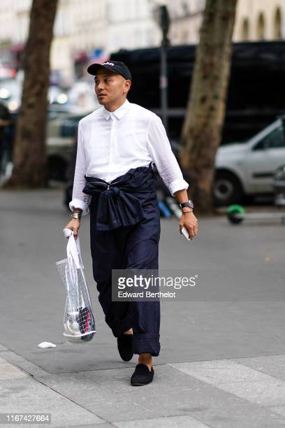 A guest wears a black cap a white shirt dark navy cuffed pants bracelets a transparent tote bag black slippers outside White Mountaineering during...