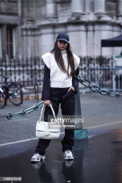 Guest wears a black cap, a white wool turtleneck sleeveless pullover, a black top, black sport pants, sneakers shoes, a white quilted Chanel bag ,...