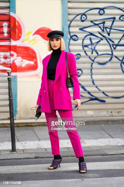 Guest wears a black cap hat, a black turtleneck pullover, a neon pink oversized blazer jacket, neon pink suit pants, purple leather quilted pointy...