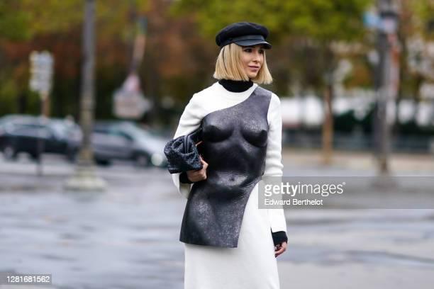 Guest wears a black cap hat, a black turtleneck top, a white dress, a black shiny bustier piece of outfit, a black leather Bottega Veneta bag,...