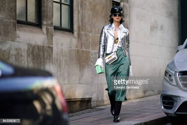 A guest wears a black cap hat sunglasses a silver shiny glitter blazer jacket a green skirt a white bag during London Fashion Week February 2018 on...
