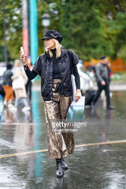 A guest wears a black cap with a rhinestone Chanel brooch a black turtleneck a black quilted jacket with cap sleeves golden lamed widelegs pants...