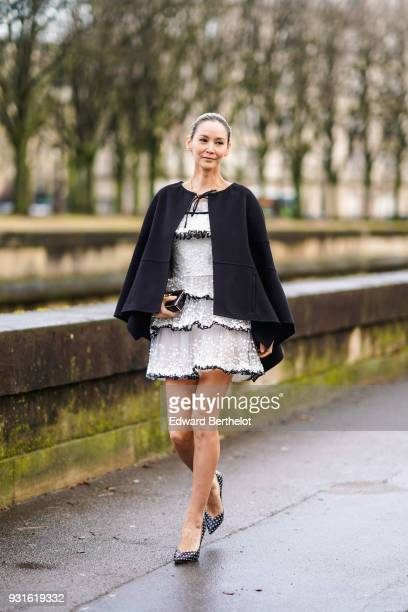 A guest wears a black cape a white tulle tiered minidress a black clutch black pumps with white polka dots outside Valentino during Paris Fashion...