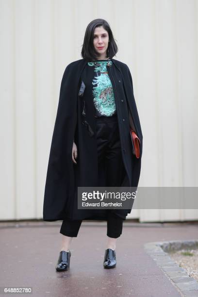 A guest wears a black cape black pants a black top with a blue print a brown clutch and black leather shoes outside the Hermes show during Paris...
