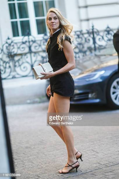 A guest wears a black chinese style top with a white inner lining mandarincollar a black belt black shorts a white clutch brown strappy sandals...