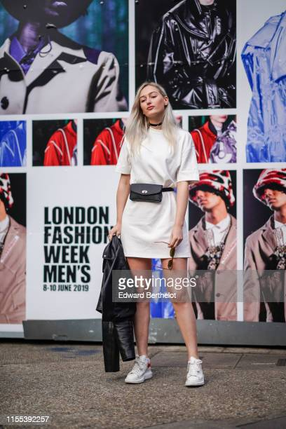 Guest wears a black choker necklace, a t-shirt white dress, a black belt bag and Alexander McQueen white and red sneakers, during London Fashion Week...