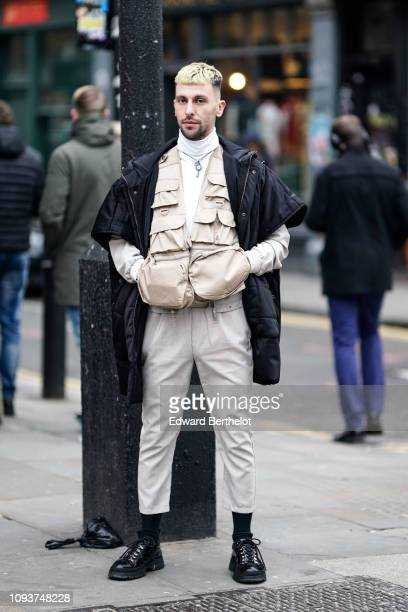 A guest wears a black coat a beige tactical jacket white cropped pants black leather shoes during London Fashion Week Men's January 2019 on January...