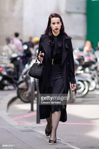 A guest wears a black coat a black skirt a black bag outside Lanvin during Paris Fashion Week Menswear SpringSummer 2019 on June 24 2018 in Paris...