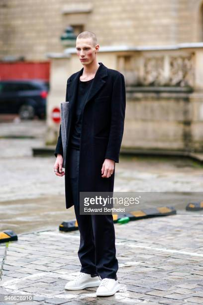A guest wears a black coat a black top black pants white sneakers outside Thom Browne during Paris Fashion Week Menswear Fall Winter 20182019 on...