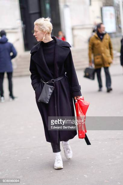 A guest wears a black coat a black turtleneck white sneakers shoes a belt bag during Paris Fashion Week Womenswear Fall/Winter 2018/2019 on March 6...
