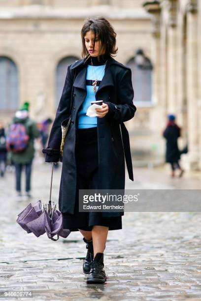A guest wears a black coat a blue top with turtleneck a black skirt black shoes outside Thom Browne during Paris Fashion Week Menswear Fall Winter...