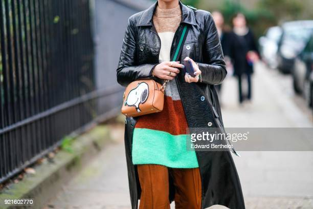 A guest wears a black coat a colored striped top a brown bag with a printed Snoopy cartoon dog during London Fashion Week February 2018 on February...
