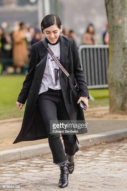A guest wears a black coat a shoulder studded strap bag a white top black pants outside Beautiful People during Paris Fashion Week Womenswear...