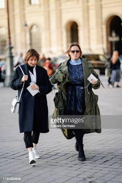 Guest wears a black coat, a white shirt, black pants, white ankle boots, a white bag ; a guest wears sunglasses, a khaki coat, a black lace dress...