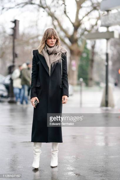 A guest wears a black coat a wool scarf white shoes outside Alexandre Vauthier during Paris Fashion Week Haute Couture Spring Summer 2020 on January...