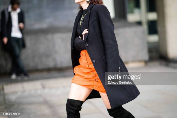 A guest wears a black coat an orange skirt black suede kneehigh boots during London Fashion Week February 2019 on February 19 2019 in London England