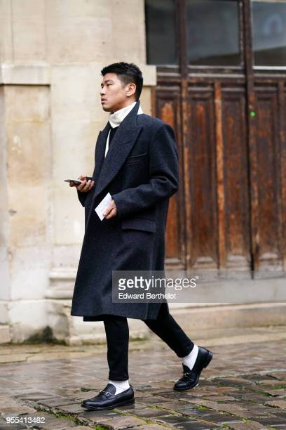 A guest wears a black coat black pants white socks black leather shoes outside Thom Browne during Paris Fashion Week Menswear Fall Winter 20182019 on...