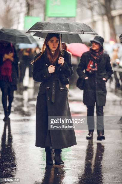 A guest wears a black coat boots holds an umbrella under the rain outside Paul Smith during Paris Fashion Week Menswear Fall Winter 20182019 on...