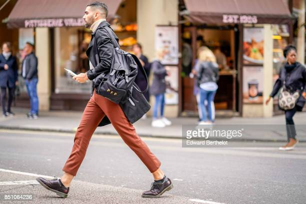 A guest wears a black coat brown pants outside JW Anderson during London Fashion Week September 2017 on September 16 2017 in London England
