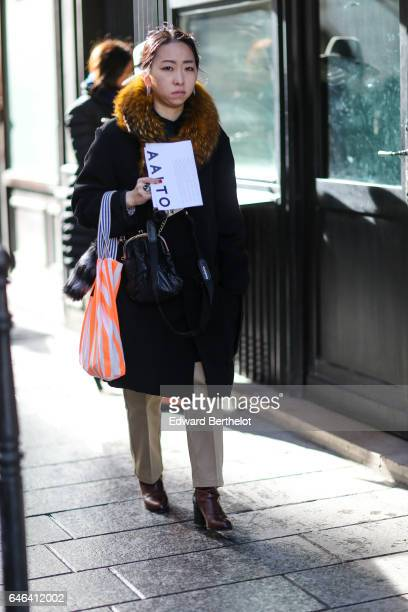 A guest wears a black coat with brown fur outside the AALTO show during Paris Fashion Week Womenswear Fall/Winter 2017/2018 on February 28 2017 in...