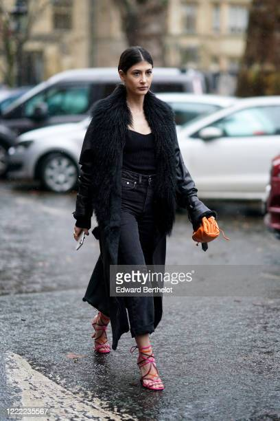 Guest wears a black coat with fluffy faux fur lapels, an orange leather bag, pink shoes, ripped jeans, during London Fashion Week Fall Winter 2020 on...