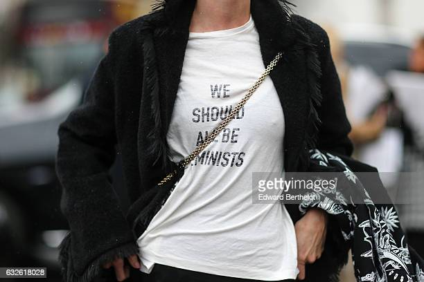 A guest wears a black coat with fur and a white tshirt with the inscription 'We should be all feminists' outside the Chanel show at the Grand Palais...