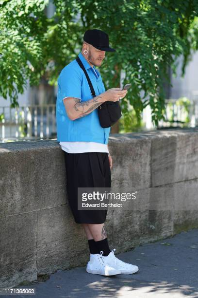 A guest wears a black corduroy cap a white earlobe enlarger a black bag a blue shirt black widelegs short pants black socks white Converse sneakers...